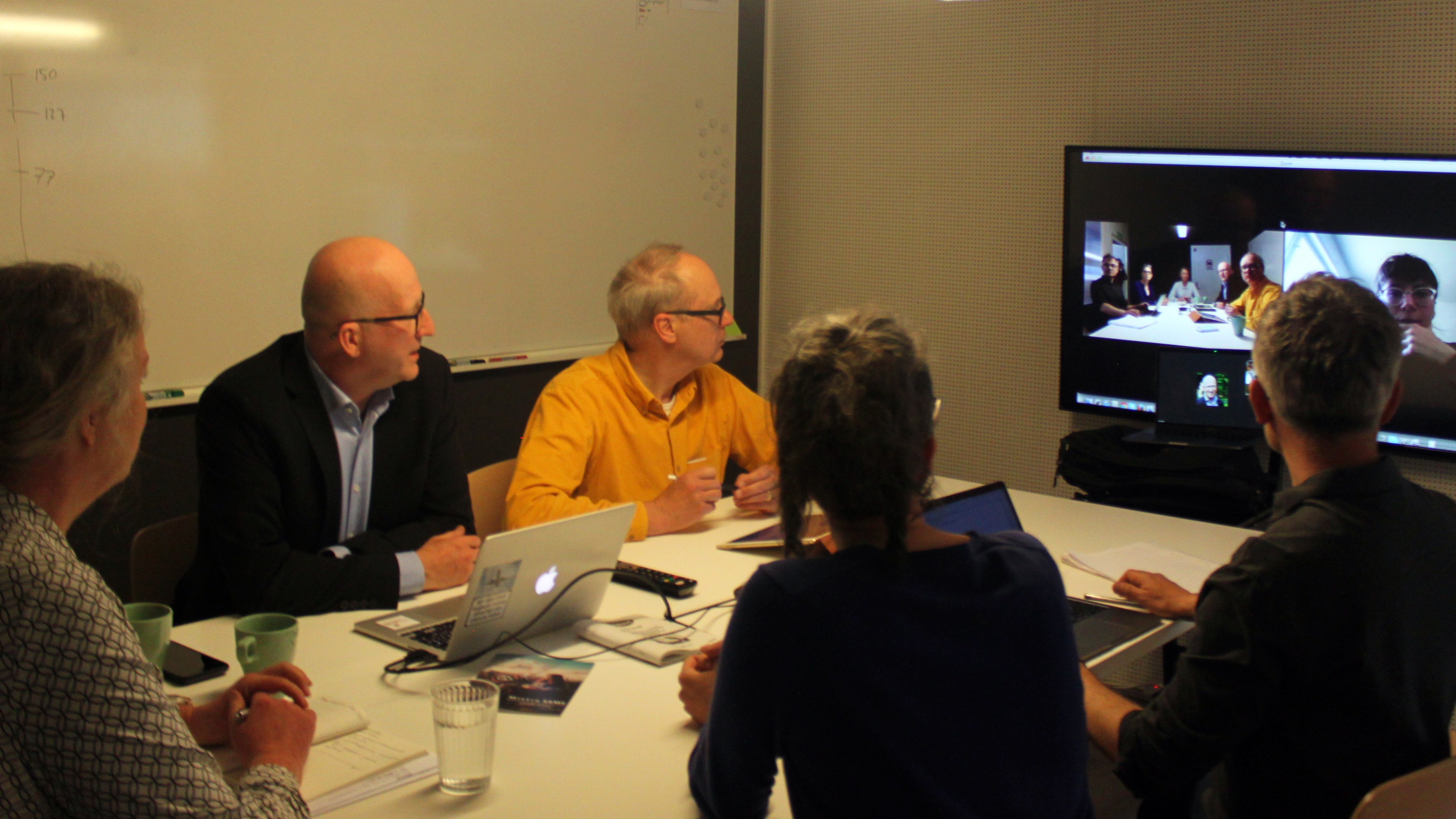 Five people around a conference table. They are looking at a screen which shows a sixth meeting participant.